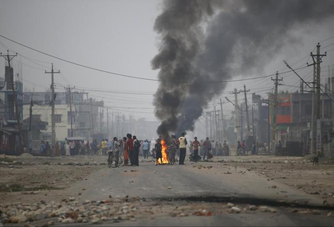 File photo of protesters standing near burning tyres as they gather to block the highway connecting Nepal and India, during a general strike called by Madhesi protesters demonstrating against the new constitution in Birgunj, Nepal November 5, 2015. Credit: Reuters/Navesh Chitrakar