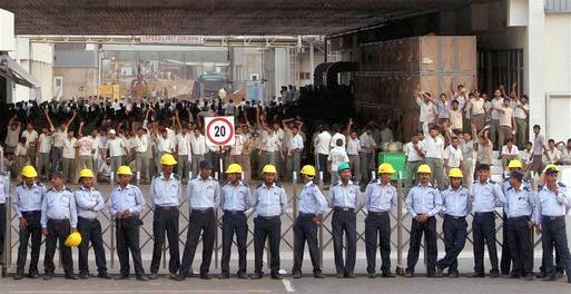 File photo of security personnel stand in front of Maruti Suzuki employees agitating for recognition of their new union at the company's plant in Manesar. Credit: PTI
