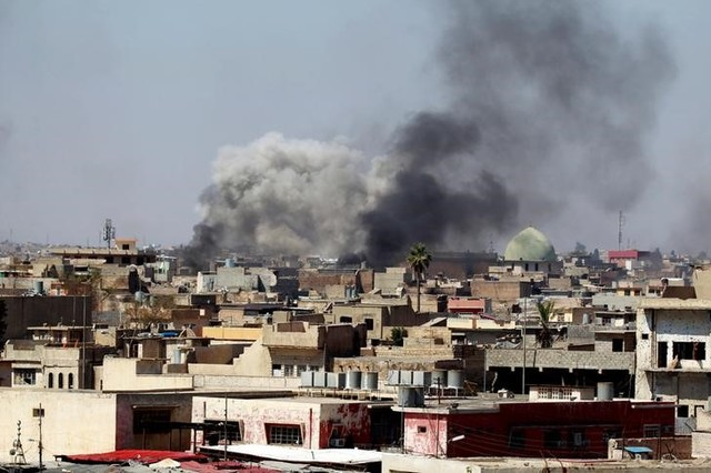 Smoke rises over the city during clashes between Iraqi forces and ISIS militants, in Mosul, Iraq March 25, 2017. Credit: Reuters