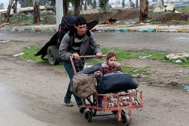 A displaced Iraqi carries his daughter in a cart to reach a safe area, as Iraqi forces battle with Islamic State militants, in the city of Mosul, Iraq March 18, 2017. Credit: Reuters/Youssef Boudlal
