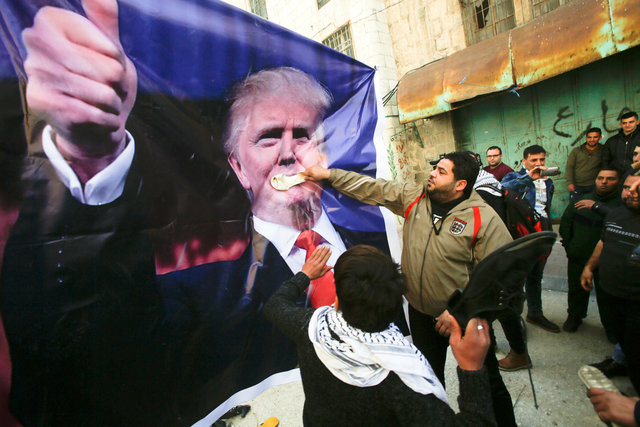 Palestinian demonstrators throw shoes on a poster depicting US President Donald Trump during a protest in the West Bank city of Hebron February 24, 2017. Credit: Reuters
