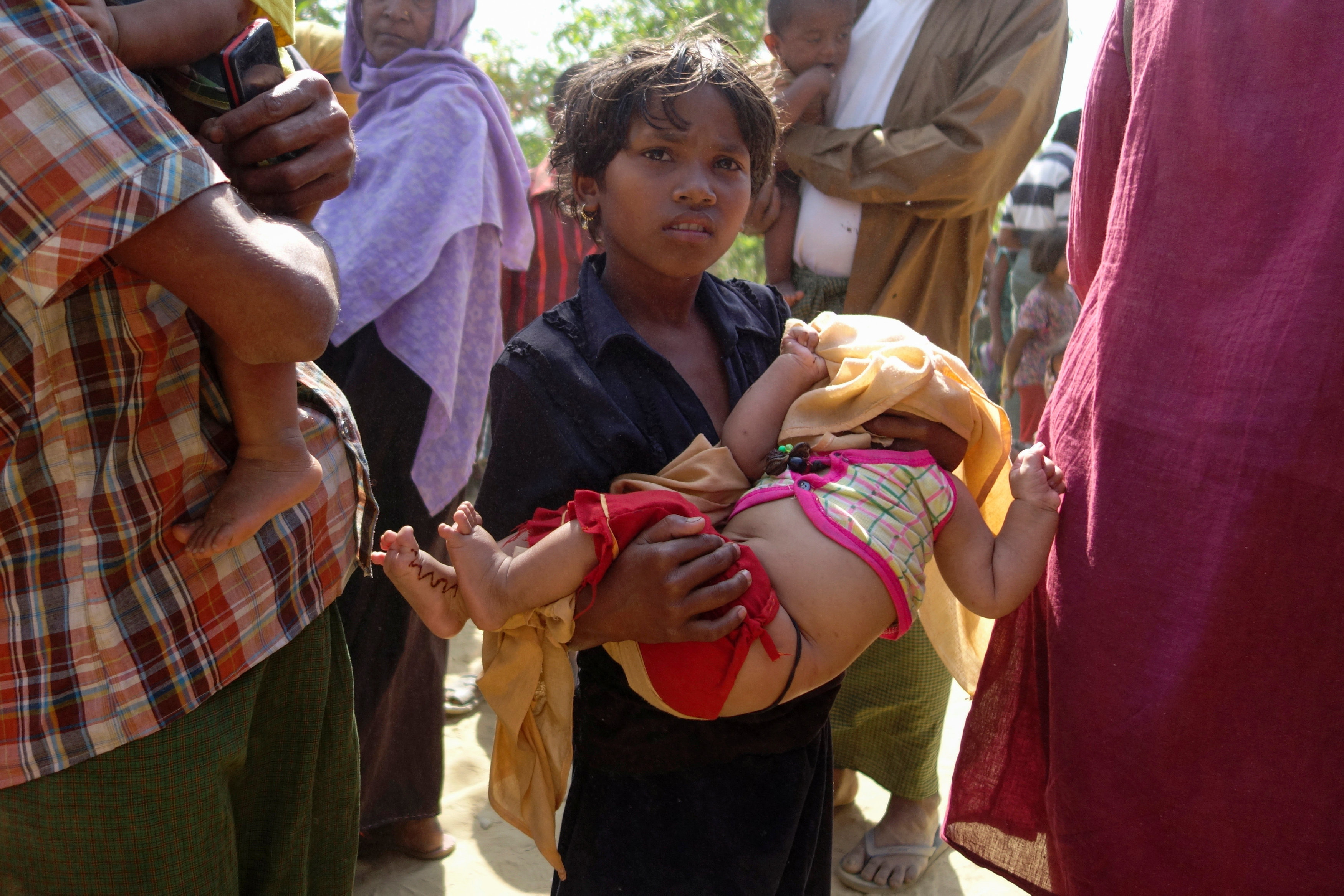 A Rohingya refugee girl carries a baby outside the food distribution center at Kutupalang unregistered Refugee Camp in Cox's Bazar, Bangladesh, February 27, 2017. Credit: Reuters/Claudia Jardim
