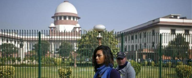 People walk past the Supreme Court. Credit: Reuters