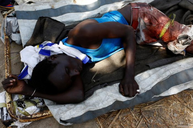 A wounded man lies on a stretcher following an armed confrontation between two communities, in Thonyor, Leer state, South Sudan, February 25, 2017. Credit: Siegfried Modola/Reuters
