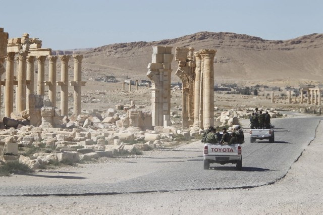 Syrian army soldiers drive past the Arch of Triumph in the historic city of Palmyra, in Homs Governorate, Syria in this April 1, 2016 file photo. Credit: Reuters