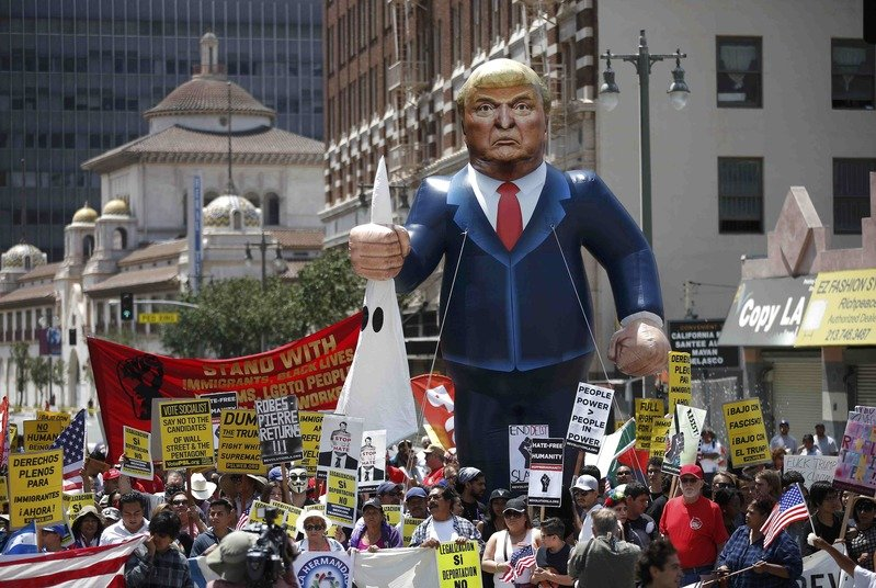 People march with an inflatable effigy of Donald Trump during an immigrant rights protest. Credit: Reuters/Files