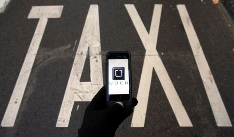 The logo of car-sharing service app Uber on a smartphone over a reserved lane for taxis in a street is seen in this photo illustration taken December 10, 2014. Credit: Reuters/Sergio Perez/Illustration/Files