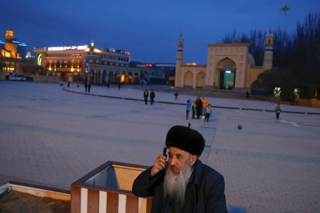 An ethnic Uighur man talks on the phone in front of the Id Kah Mosque in the old town of Kashgar, Xinjiang Uighur autonomous region, China, March 22, 2017. Credit: Reuters