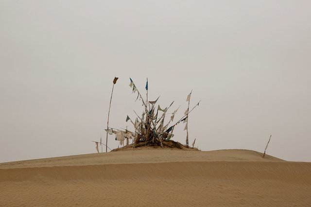Flag-festooned poles stand over a grave in the cemetery surrounding the tomb of Imam Asim in the Taklamakan desert outside the village of Jiya near Hotan, Xinjiang Uighur Autonomous Region, China, March 21, 2017. Credit: Reuters