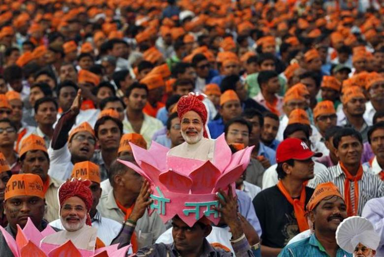 A supporter of Gujarat's chief minister Narendra Modi, the prime ministerial candidate for Bharatiya Janata Party (BJP), wears a headgear with a portrait of Modi during a rally being addressed by Modi ahead of the 2014 general elections, in Ahmedabad February 20, 2014. REUTERS/Amit Dave