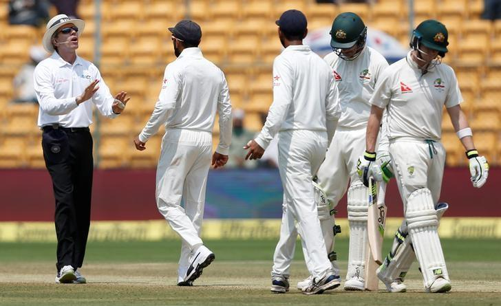 Cricket - India v Australia - Second Test cricket match - M .Chinnaswamy Stadium, Bengaluru, India - 07/03/17. India's captain Virat Kohli (2nd L) speaks to the umpire as Australia's captain Steven Smith (R) walks off the ground after being dismissed. Credit: Reuters/Danish Siddiqui