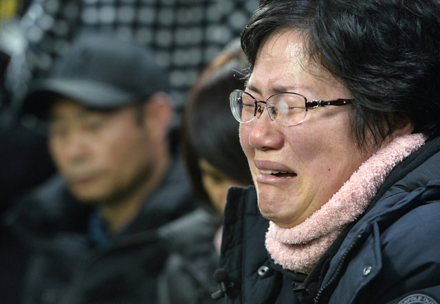 A family member of a missing passenger onboard sunken ferry Sewol cries during its salvage operations at the sea off Jindo, South Korea, March 23, 2017. Credit: Reuters