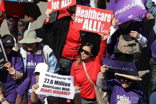 """People march in a """"Save Obamacare"""" rally on the seventh anniversary of Obamacare's signing, in Los Angeles, California, US March 23, 2017. Credit: Reuters"""