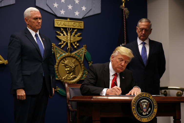 US President Donald Trump signs the original executive order in January. Credit: Carlos Barria/Reuters