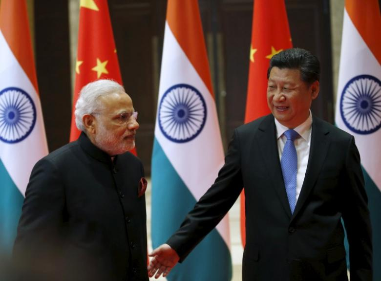 Chinese President Xi Jinping (R) guides Indian Prime Minister Narendra Modi to a meeting room in Xian, Shaanxi province, Chin. Credit: Reuters/Kim Kyung-Hoon