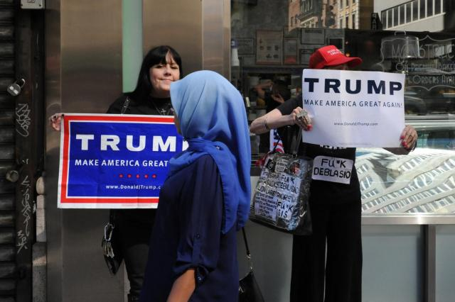 A woman wearing a Muslim headscarf walks past people holding Donald Trump signs before the start of the annual Muslim Day Parade in Manhattan. Credit: Reuters  REUTERS/Stephanie Keith