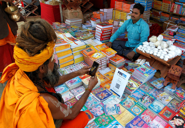 A Sadhu or a Hindu holy man pays the vendor through Paytm, a digital wallet company, after buying a book during the annual religious festival of Magh Mela in Allahabad, India, January 26, 2017. Picture taken January 26, 2017. Credit: Reuters