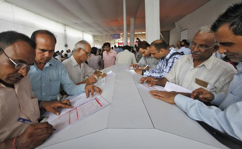 Tax payers fill up forms before submitting their income tax returns on the last day of filing in New Delhi July 31, 2013. Indian government revenues are expected to increase by 21 percent in the 2013/2014 fiscal year, Finance Minister P Chidambaram said on Wednesday. REUTERS/Anindito Mukherjee (INDIA - Tags: BUSINESS) - RTX125QG
