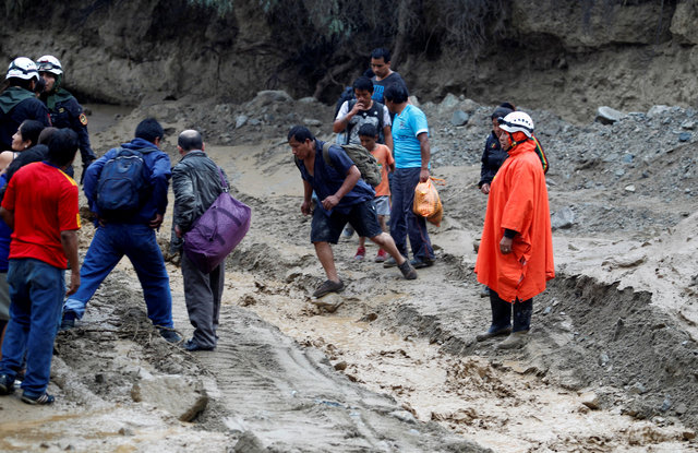 Residents try to cross a mudslide near the central highway after the Rimac river overflowed in Huarochiri, Lima, Peru, March 23, 2017. Credit: Reuters