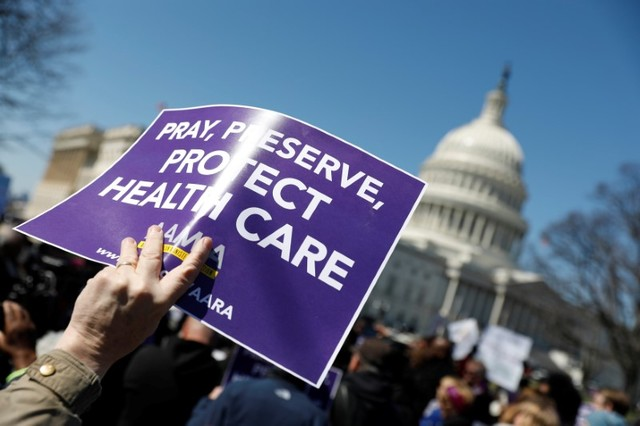 Demonstrators hold signs during a protest against the repeal of the Affordable Care Act outside the Capitol Building in Washington, US, March 22, 2017. Credit: Reuters