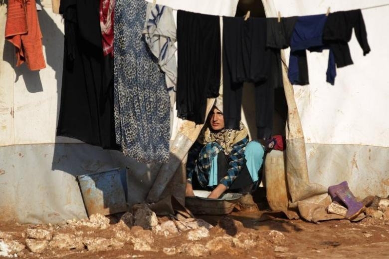 An internally displaced Syrian woman washes clothes inside her tent at the Bab Al-Salam refugee camp, near the Syrian-Turkish border, northern Aleppo province, Syria January 19, 2017. Credit: Khalil Ashawi/Reuters