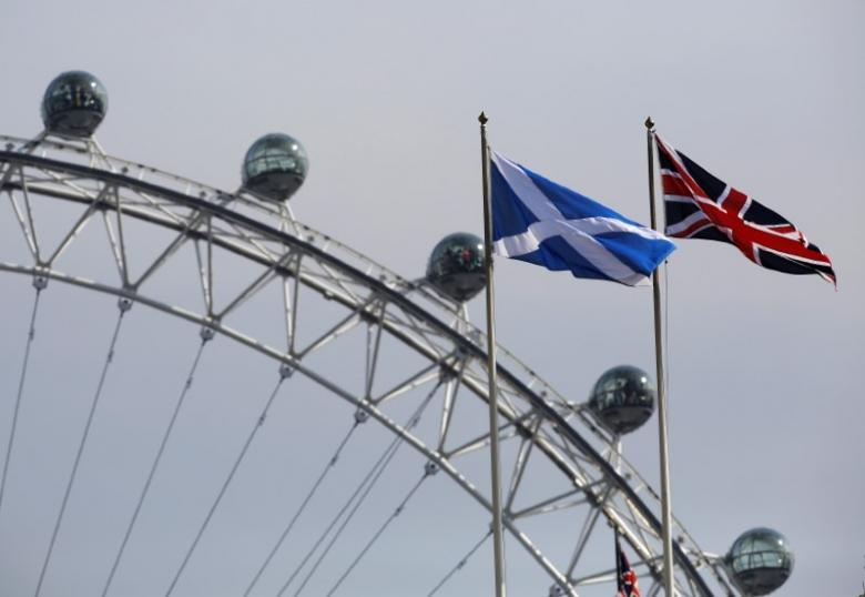 A Scottish Saltire flag and British Union flag fly together with the London Eye behind in London September 19, 2014. Credit: Reuters