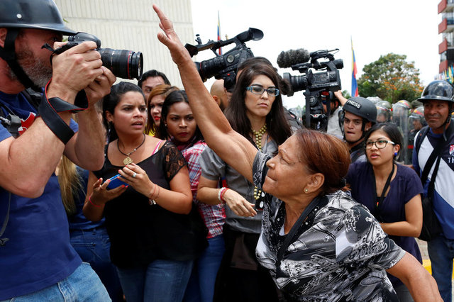 A supporter of Venezuela's President Nicolas Maduro tries to take the camera of a photographer away, during clashes with opposition supporters outside the Supreme Court of Justice (TSJ) in Caracas, Venezuela March 30, 2017. Credit: Reuters