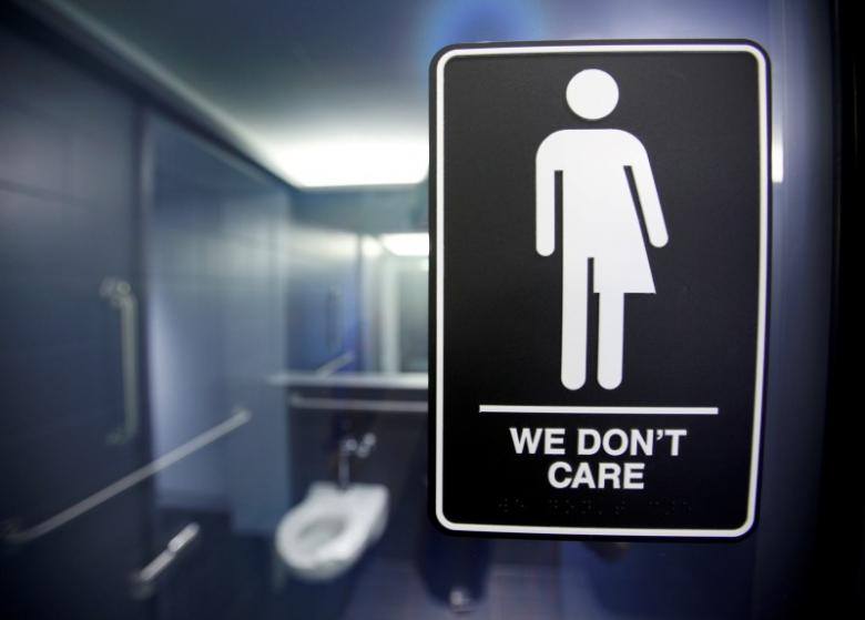 A sign is seen in the bathroom stalls at the 21C Museum Hotel in Durham, North Carolina in this May 3, 2016 file photo. REUTERS/Jonathan Drake/File photo