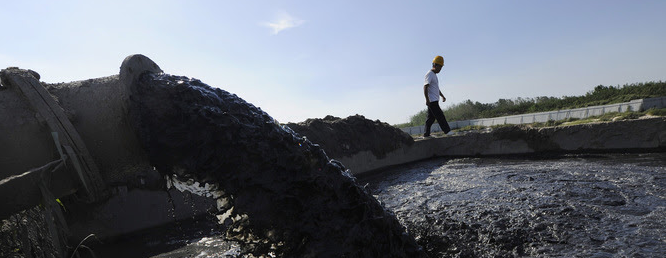 A pipe pumps polluted water from the Nanfeihe River into a treatment pool, in Hefei, Anhui province September 1, 2013. Credit: Reuters/Stringer