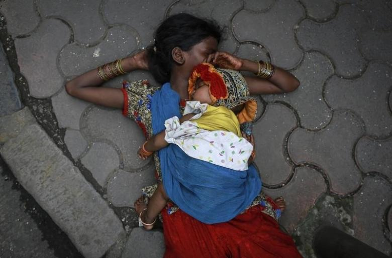 A woman sleeps with her baby on sidewalk at a market in Mumbai August 13, 2014. REUTERS/Danish Siddiqui (INDIA - Tags: SOCIETY) - RTR4292B