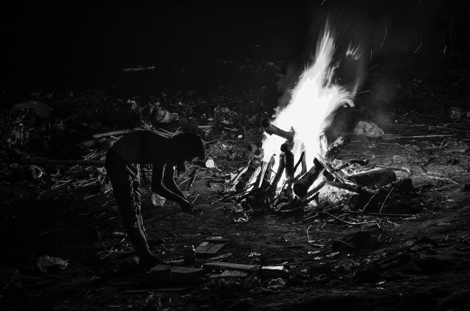 A pyre burner waits for the pyre to completely burn during night at the Ghat. Credit: Wamika Singh