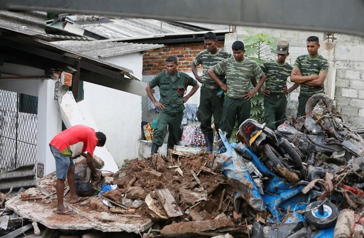 A man opens a bag next to military officers during a rescue mission after a garbage dump collapsed and buried dozens of houses in Colombo, Sri Lanka April 15, 2017. REUTERS/Dinuka Liyanawatte