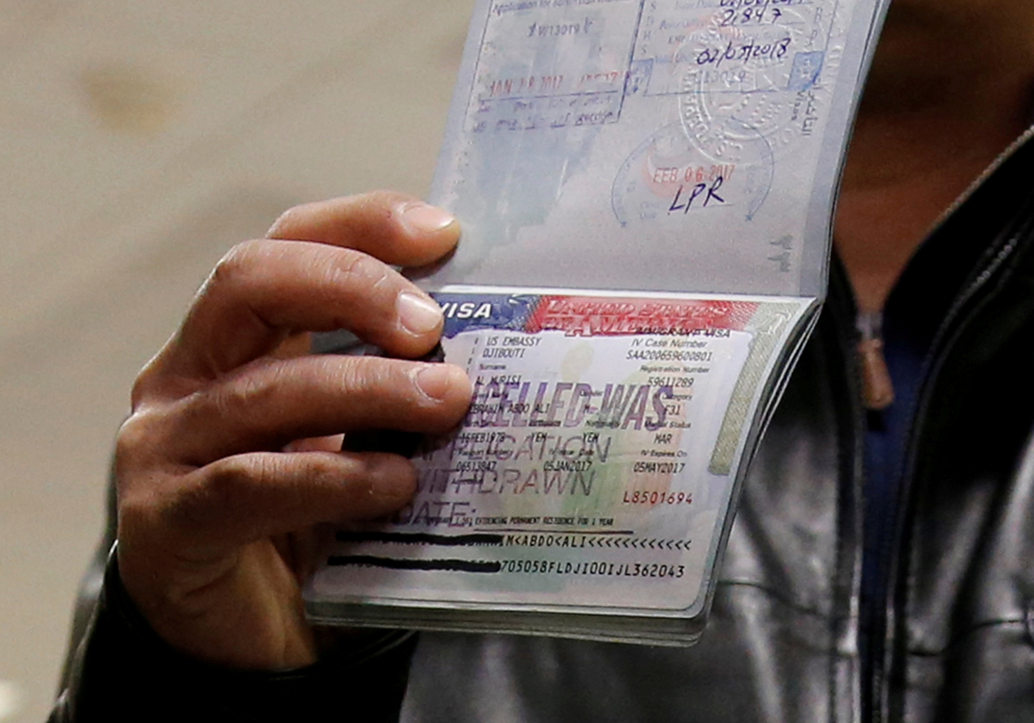FILE PHOTO: A member of the Al Murisi family, Yemeni nationals who were denied entry into the U.S. last week because of the recent travel ban, shows the cancelled visa in their passport from their failed entry to reporters as they successfully arrive to be reunited with their family at Washington Dulles International Airport in Chantilly, Virginia, US February 6, 2017. Credit: Reuters/Jonathan Ernst/File Photo