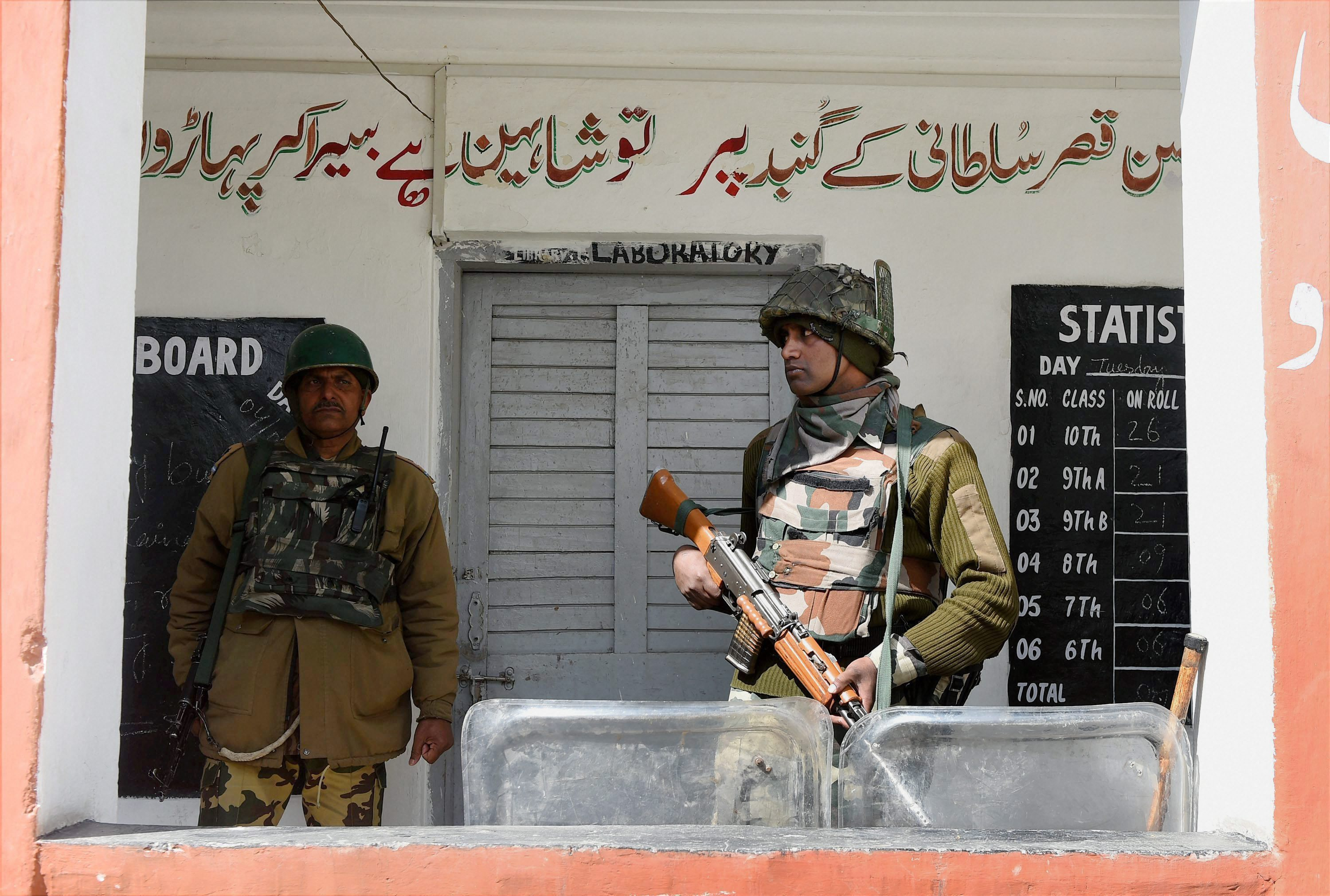 A jawan stand guard outside a polling station for Srinagar parliamentary constituency of Jammu and Kashmir at Budgam in Srinagar on Sunday. Credit: PTI/S. Irfan