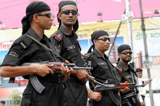 Members of the Rapid Action Battalion (RAB), in their distinctive black attire, stand guard on a street in Dhaka. Credit: Reuters/Files