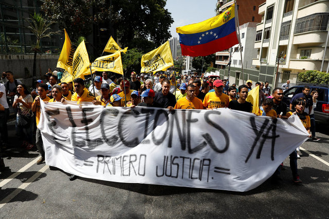 """Demonstrators carry a banner reading """"Elections now, justice first"""" during an opposition rally in Caracas, Venezuela April 4, 2017. Credit: Reuters"""