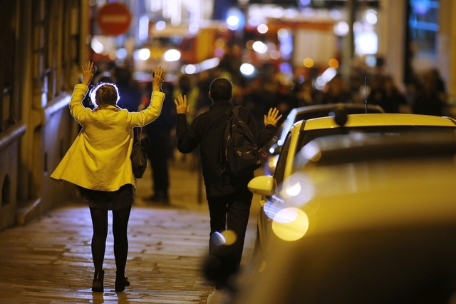People raise their arms to show their hands as they walk towards police on a side road near the Champs Elysees Avenue after shooting incident in Paris, France, April 20, 2017. Credit Reuters/Benoit Tessier