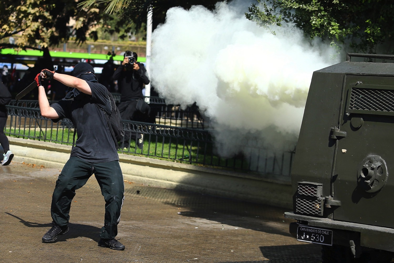 A demonstrator prepares to hit a riot police vehicle during a protest calling for changes in the education system in Santiago, Chile April 11, 2017. Credit: Reuters/Ivan Alvarado