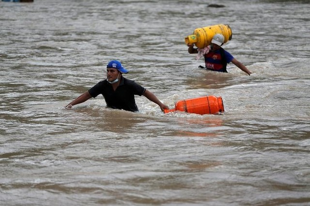 Men walk in a river with their belongings after flooding and mudslides caused by heavy rains in Mocoa, Colombia April 2, 2017. Credit: Reuters