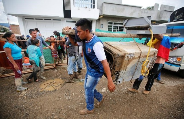 Men walk with their belongings on a street destroyed after flooding and mudslides caused by heavy rains in Mocoa, Colombia April 2, 2017. Credit: Reuters
