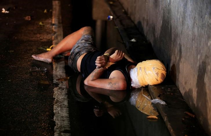 The body of a dead man with his head wrapped with masking tape, whom police said was a victim of a drug-related vigilante execution, lays on a street in Pasay city, metro Manila, Philippines November 15, 2016. Credit: Reuters/Romeo Ranoco/Files