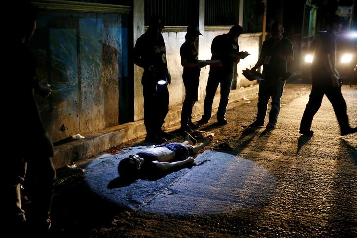 Police investigate the body of Herman Cunanan, whom police said was killed by men riding in two motorcycles, in Quezon city, Metro Manila, Philippines October 19, 2016. Credit: Reuters/Erik De Castro/Files