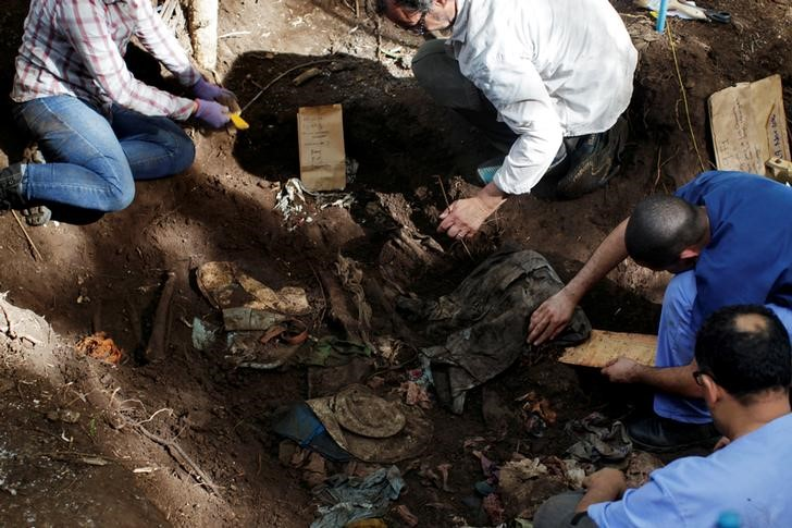 Members of the forensic team and auxiliary workers work at an exhumation site in the village of La Joya as they search for human remains of the EL Mozote massacre in the town of Meanguera, El Salvador, November 24, 2016. Credit: Reuters/Jose Cabezas