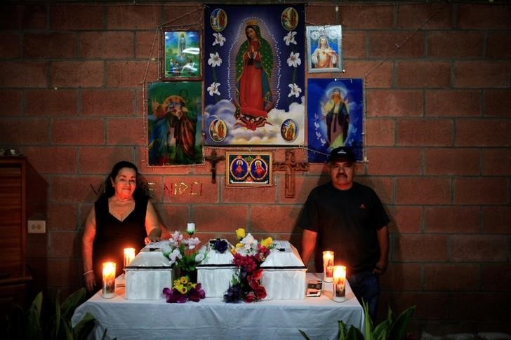 Nila Torres and Ernesto Torres pose for a picture with the remains of their family members who died in the El Mozote massacre, during their wake, in the village of La Joya, Meanguera, El Salvador, December 10, 2016. Credit: Reuters/Jose Cabezas
