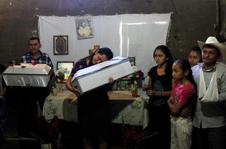 Members of the Torres and Ramos families pose for a photograph with the remains of Petrona Chavarria and Vilma Ramos who died in the El Mozote massacre, in the village of La Joya, Meanguera, El Salvador, December 11, 2016. Credit: Reuters/Jose Cabezas