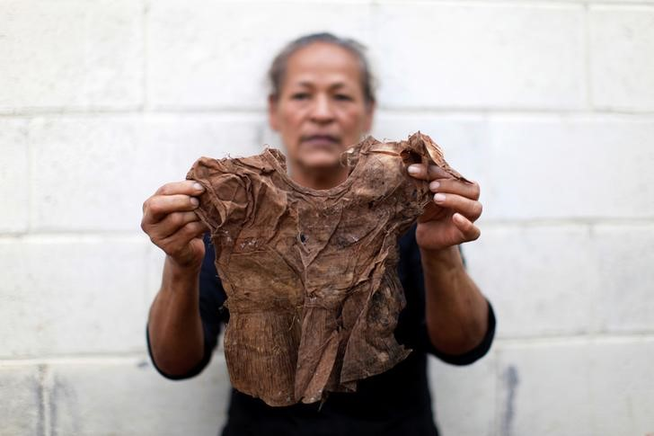 Miriam Marquez holds the dress of a relative found in a mass grave on her property during ongoing excavations in the village of El Mozote, in the town of Meanguera, El Salvador, November 24, 2016. Credit: Reuters/Jose Cabezas