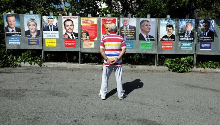 """A man looks at campaign posters of the 11th candidates who are running in the 2017 French presidential election ,in Saint Andre de La Roche, near Nice, France, April 10, 2017. L-R : Nicolas Dupont-Aignan, Debout La France group candidate, Marine Le Pen, French National Front (FN) political party leader, Emmanuel Macron, head of the political movement En Marche ! (Onwards !), French Socialist party candidate Benoit Hamon, Nathalie Arthaud, France's extreme-left Lutte Ouvriere political party (LO) leader, Philippe Poutou, Anti-Capitalist Party (NPA) presidential candidate, Jacques Cheminade, """"Solidarite et Progres"""" (Solidarity and Progress) party candidate, lawmaker and independent candidate Jean Lassalle, Jean-Luc Melenchon, candidate of the French far-left Parti de Gauche, Francois Asselineau, UPR candidate, and Francois Fillon, the Republicans political party candidate. Credit: Reuters/Eric Gaillard/Files"""