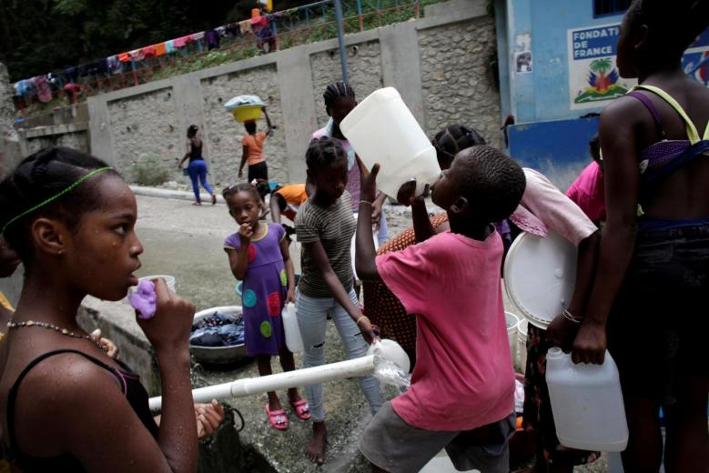 A boy drinks drinkable water from a container at a source in Port-au-Prince, Haiti. Credit: Reuters/Andres Martinez Casares