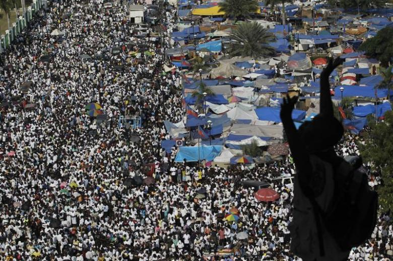 An earthquake survivor holds up his arms as he prays while a crowd gathers downtown in commemoration of the January 12 earthquake at Port-au-Prince February 12, 2010. Credit: Reuters/Ivan Alvarado