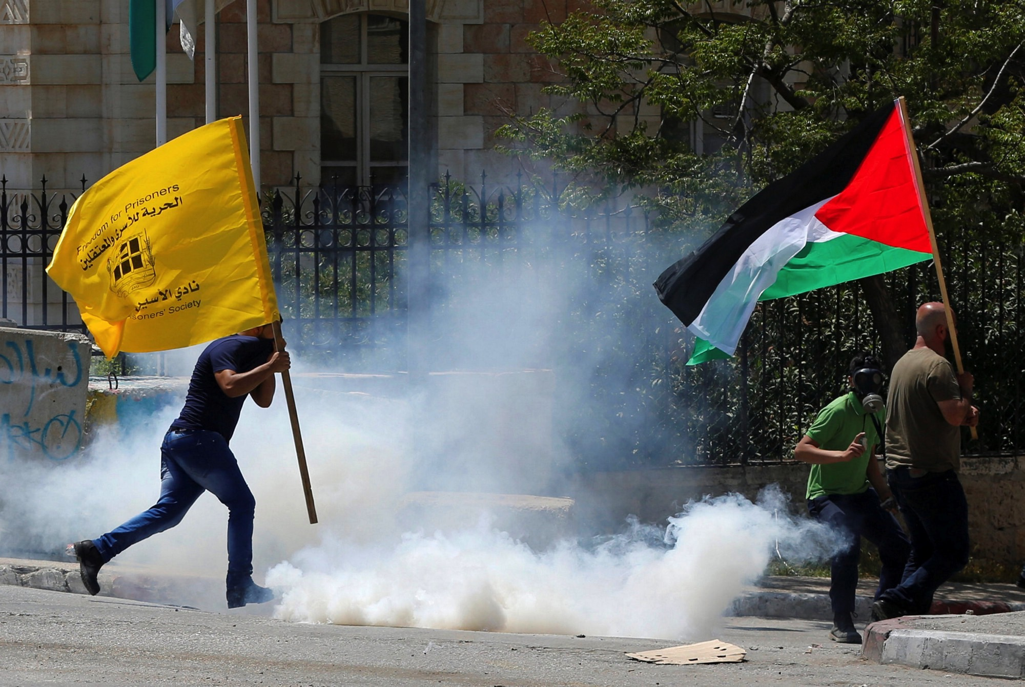 Palestinian protesters run for cover from tear gas canisters fired by Israeli troops during clashes following a protest in solidarity with Palestinian prisoners held by Israel, in the West Bank town of Bethlehem April 17, 2017. Credit: Reuters/Ammar Awad